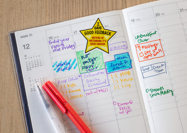 Yellow star sticker stuck in busy day planner