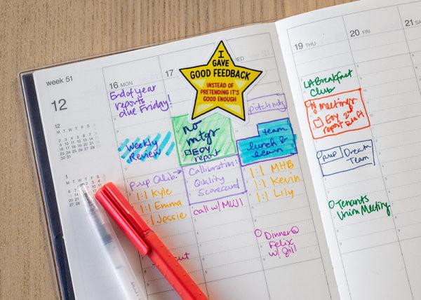 Yellow star sticker stuck in busy day planner