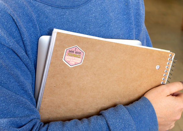 Person in blue sweatshirt holding a laptop and spiral notebook with sticker on the back of the notebook