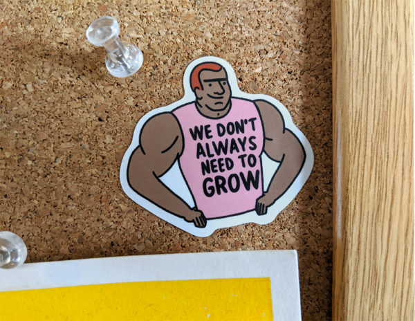 "Sticker of a muscle man in a pink tank top that reads ""we don't always need to grow"" stuck to a bulletin board"