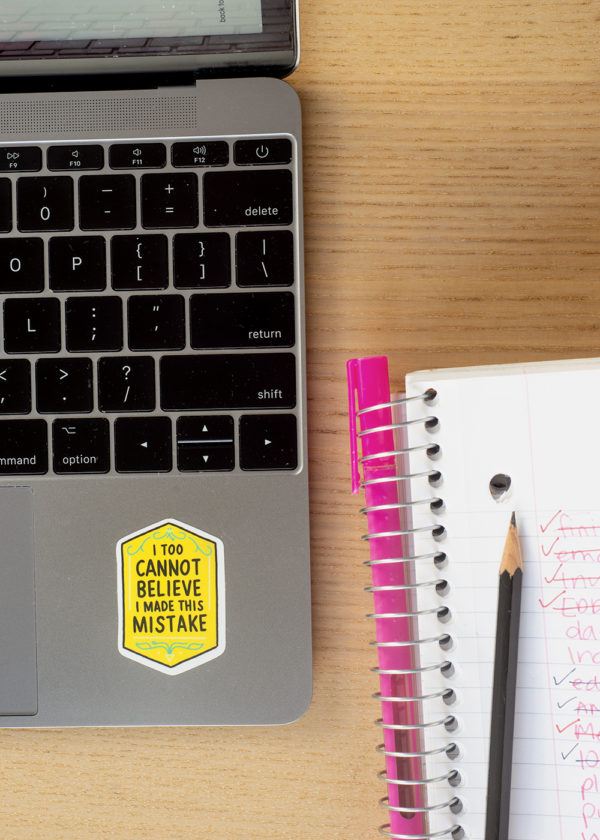 "Yellow sticker that says ""I too cannot believe I made this mistake"" on laptop keyboard next to a notebook, highlighter, and sharp pencil."